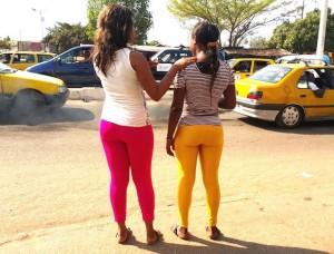 Deux jeunes filles en legging faisant du stop au bord d'une route de Conakry